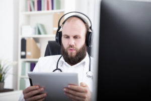 Bearded man with headphones and tablet computer.